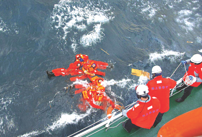 Japanese Coast Guard personnel fish crew members of Ming Guang out of the chilly waters between Honshu and Hokkaido islands on Friday. The crew members abandoned ship after it started listing and finally sank. Photo: AFP